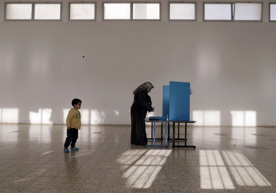 An Israeli Arab stands behind a voting booth before casting her ballot at a polling station in the n