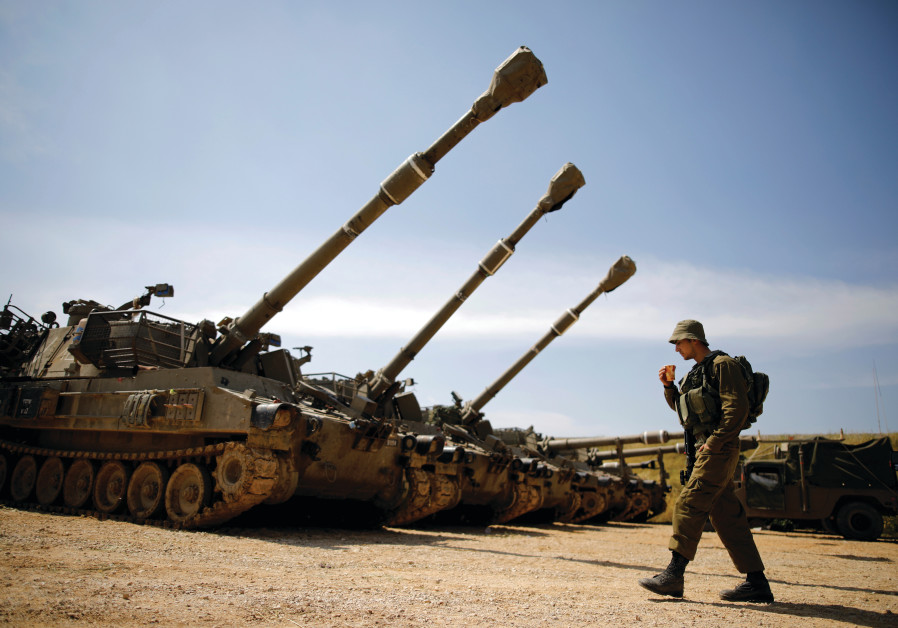 A soldier stands near a battery of cannons near the Gaza border, March 28th, 2019