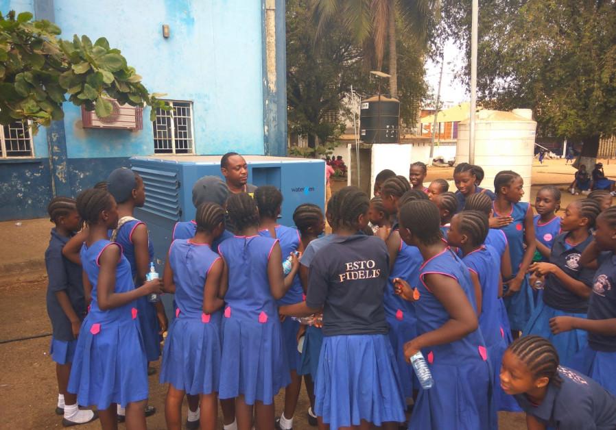 Schoolchildren receiving clean, fresh water on campus.
