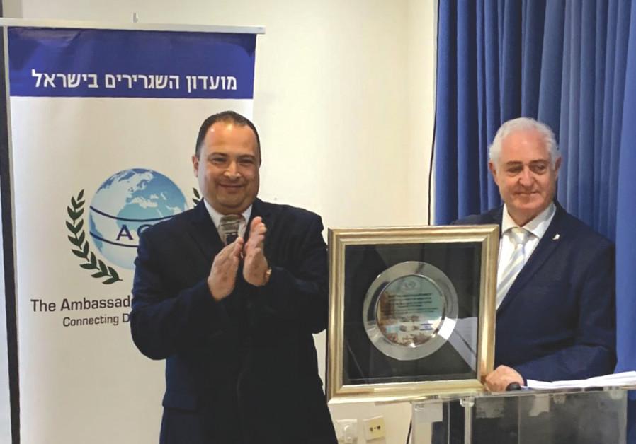 GUATEMALAN AMBASSADOR Mario Bucaro (left) receives the Award of Merit from Ambassadors' Club Preside