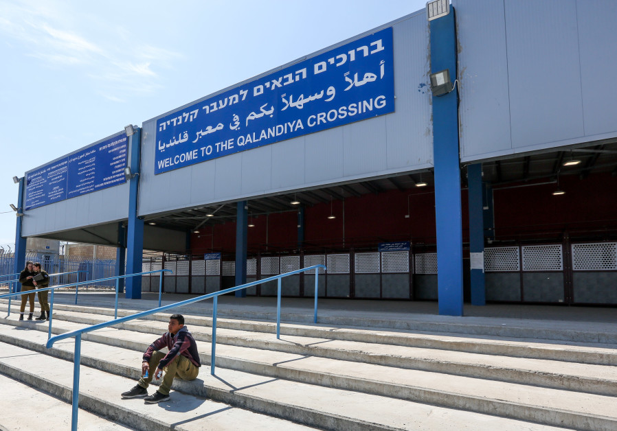 A young Palestinian sits and two IDF soldiers stand at the entrance of the Qalandiya crossing, 2019.