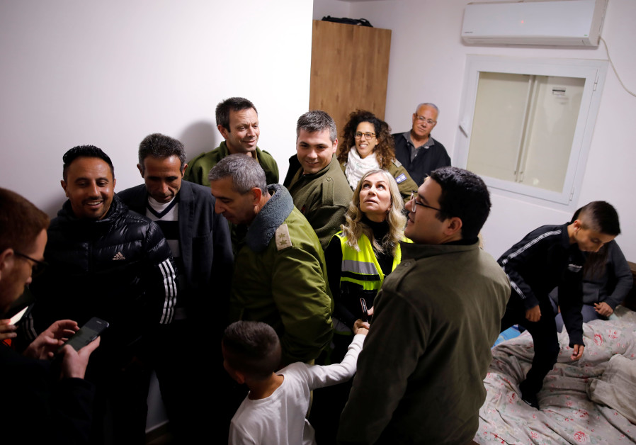 Residents and security personnel gather in a bomb shelter inside a house that was hit earlier