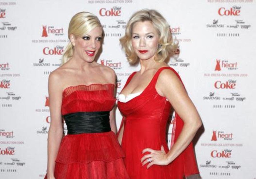 Actresses Tori Spelling (L) and Jennie Garth arrive for the Heart's Truth Red Dress collection show