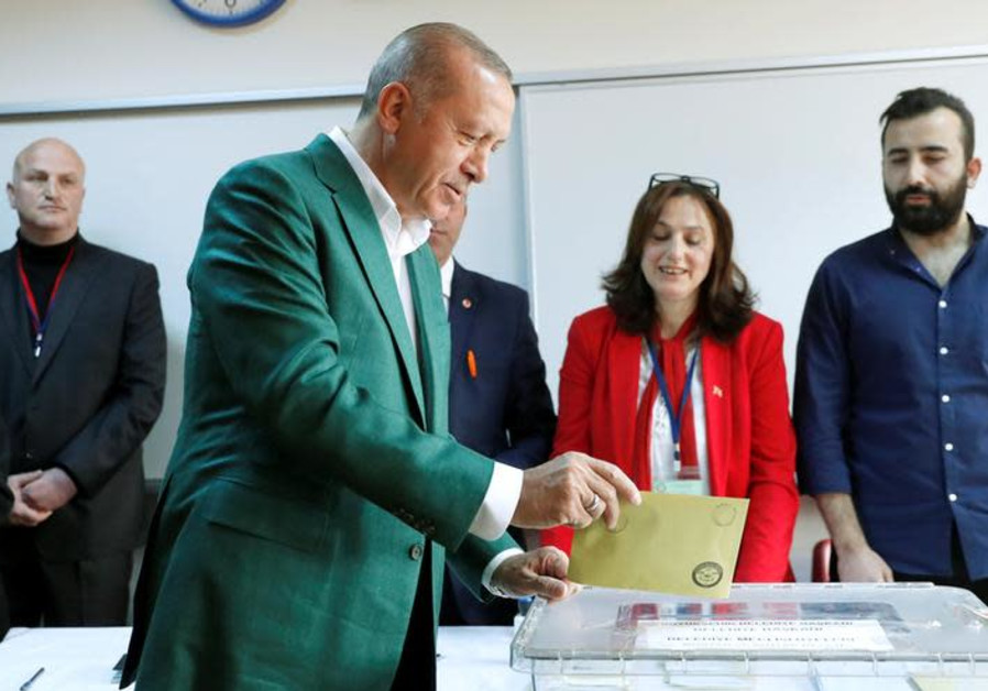 Turkish President Tayyip Erdogan casts his ballot at a polling station during the municipal election