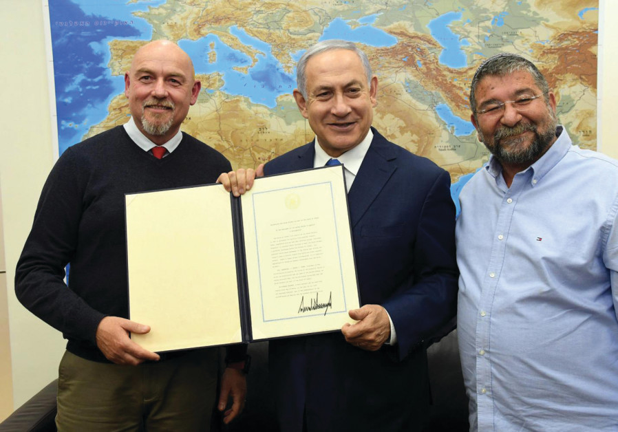 PRIME MINISTER Benjamin Netanyahu shows an executive order signed by US President Donald Trump
