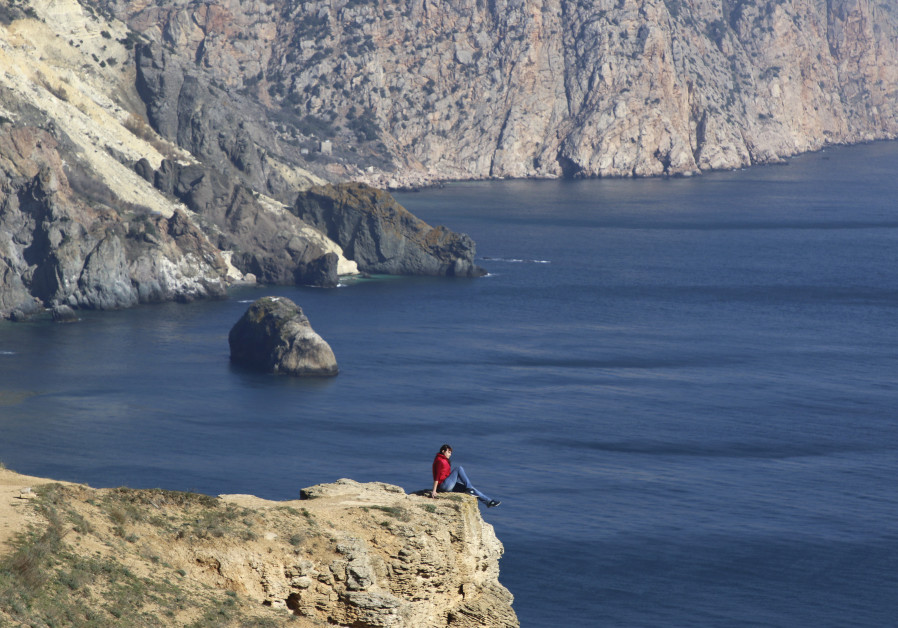 A woman sits on the edge of a cliff as she visits Cape Fiolent in the Black Sea port of Sevastopol