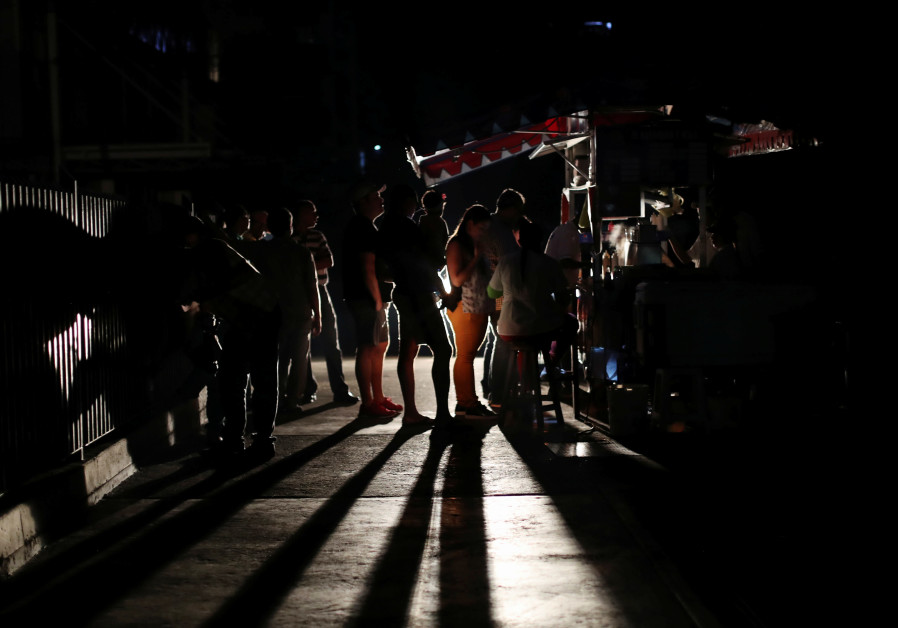 Locals gather at a street food cart during a blackout in Caracas