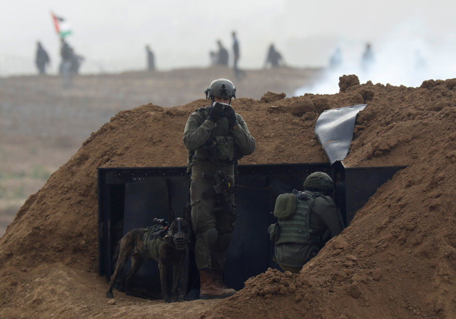 Israeli soldiers wait in position near the border fence between Israel and the Gaza Strip