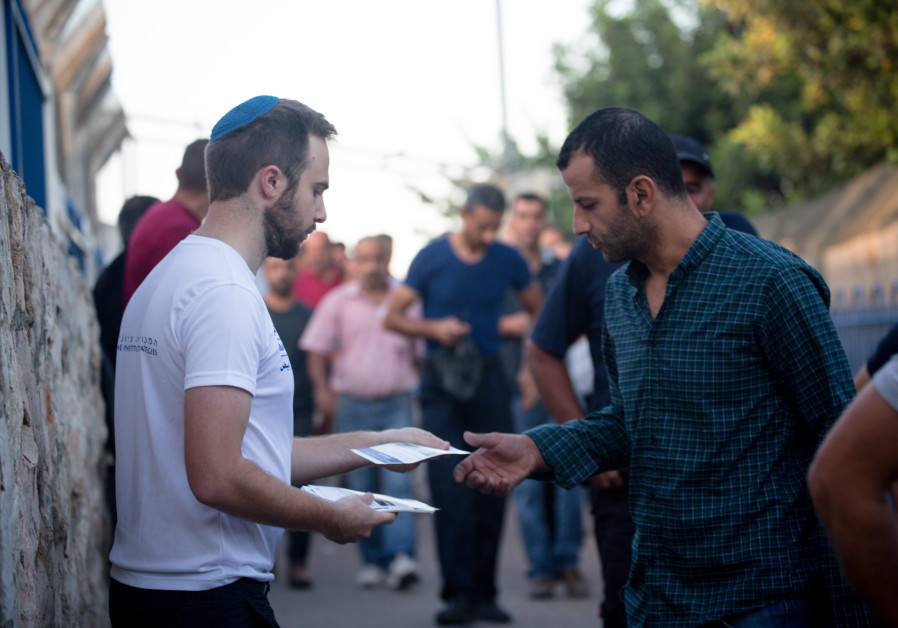 A representative for Blue & White Human Rights offering pamphlets to Palestinians. (Courtesy of Laura Ben David)