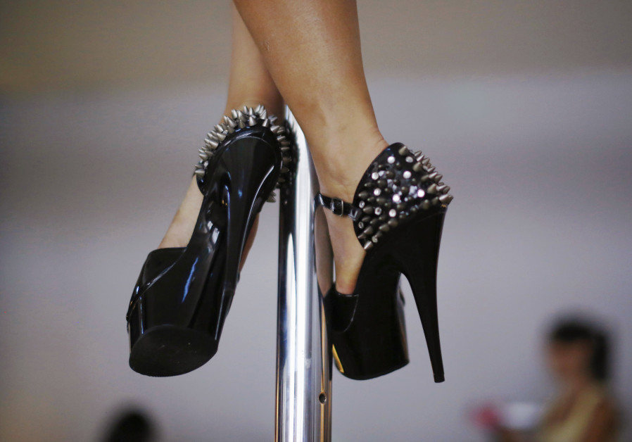 A woman wears spiked stilettos as she practises a pole dancing move during an International Women's
