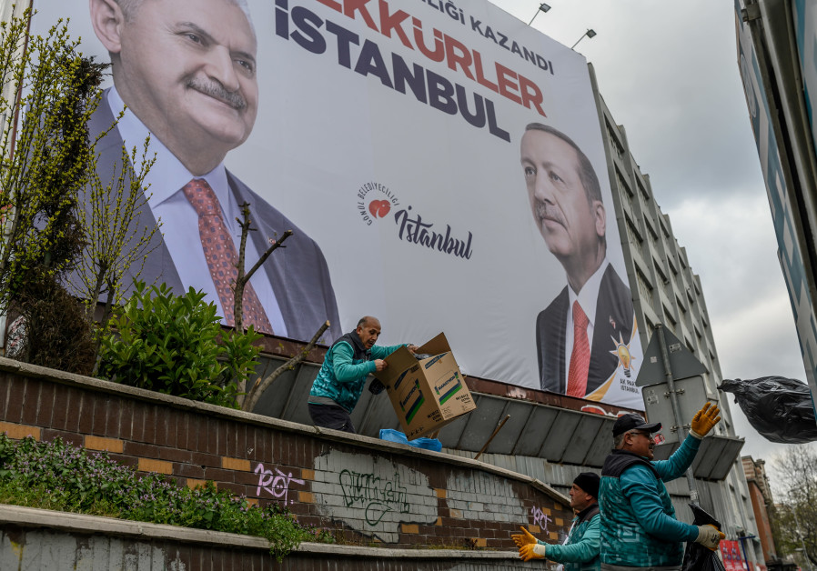 "Workers pick up the garbage next to a billboard reading ""Thank You Istanbul"""