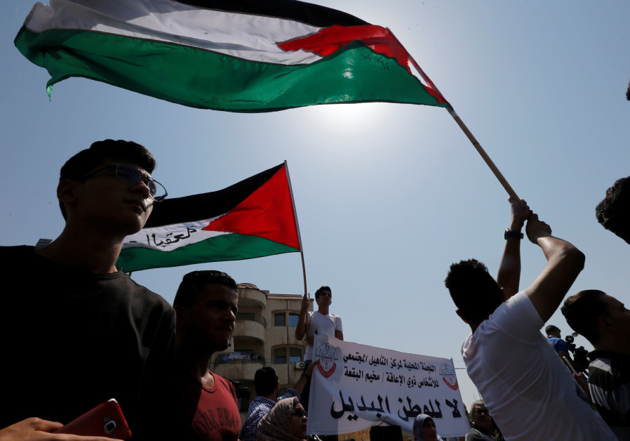 Palestinian refugees hold Palestinian flags and chant slogans during a protest in front of UNRWA off