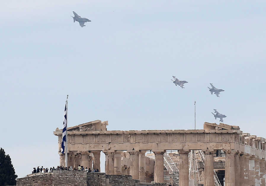 A formation of military fighting jets fly over the ancient Parthenon temple for a photo opportunity