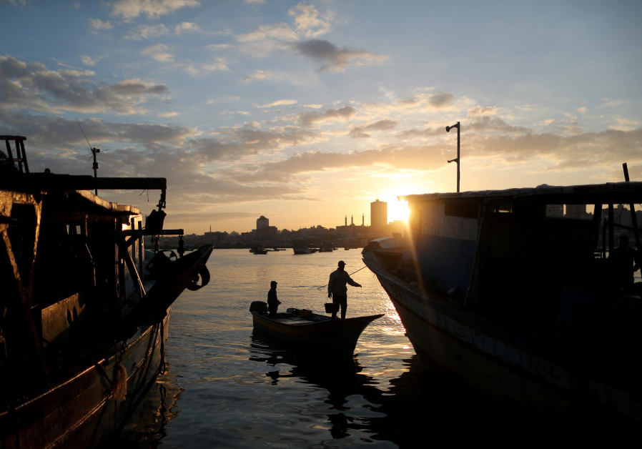 The sun rises as fishermen are seen at the seaport of Gaza City, April 2, 2019