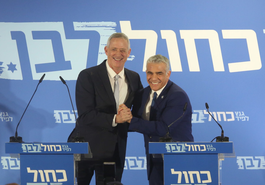 Blue and White leaders Benny Gantz (L) and Yair Lapid (R) embrace
