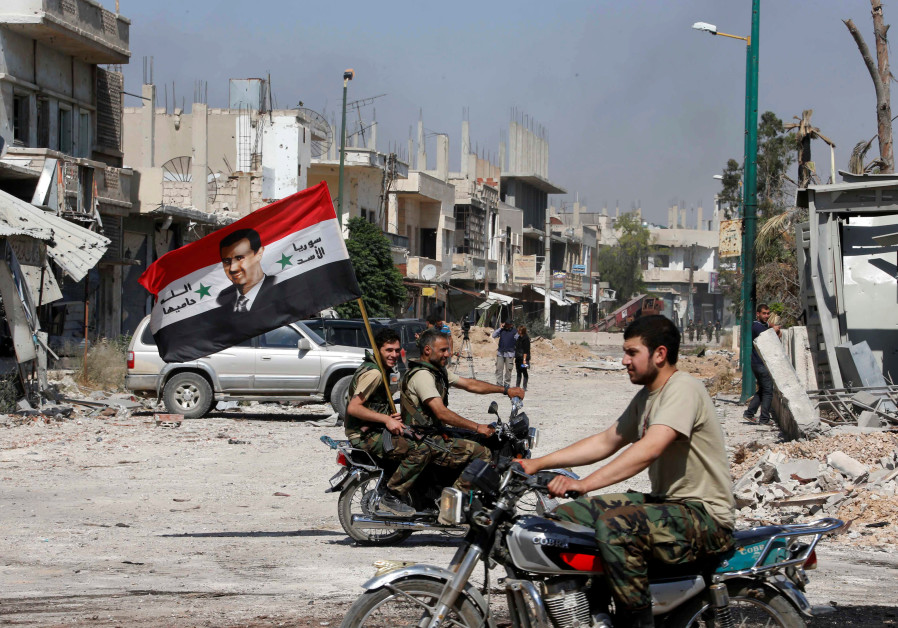Forces loyal to Syria's President Bashar al-Assad carry the national flag as they ride on motorcycle