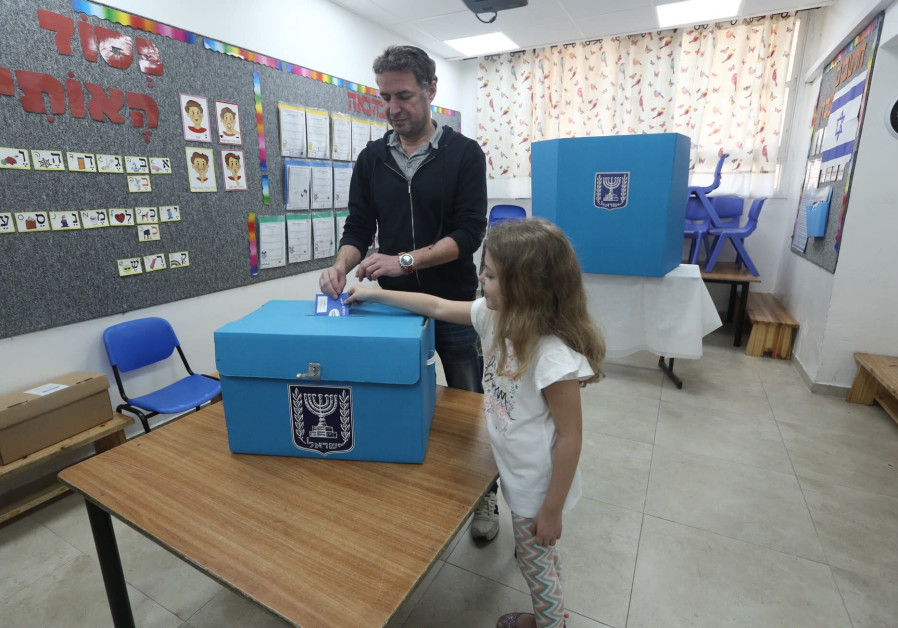 A child helps cast a vote by placing a ballot in a box in Jerusalem's Baka neighborhood