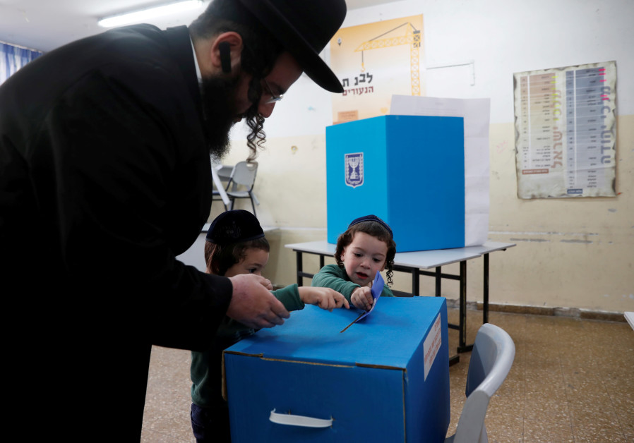 An ultra-Orthodox Jewish man helps kids cast his ballot at a polling station on April 9, 2019