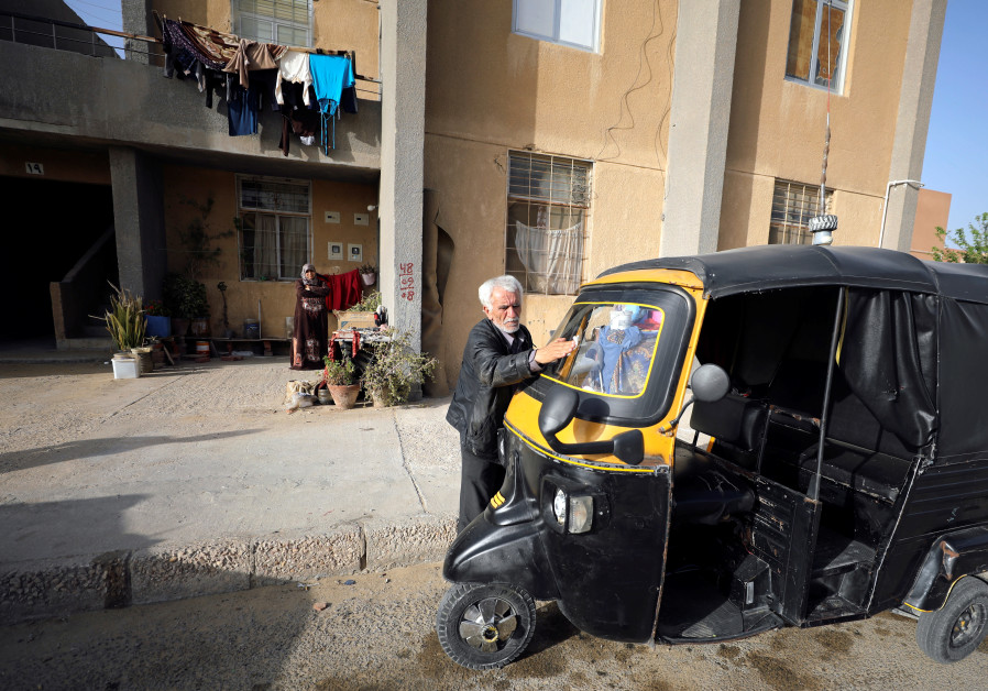 Syrian refugee Ahmad al-Khatib cleans his auto rickshaw as his wife Ilham Mohammad watches