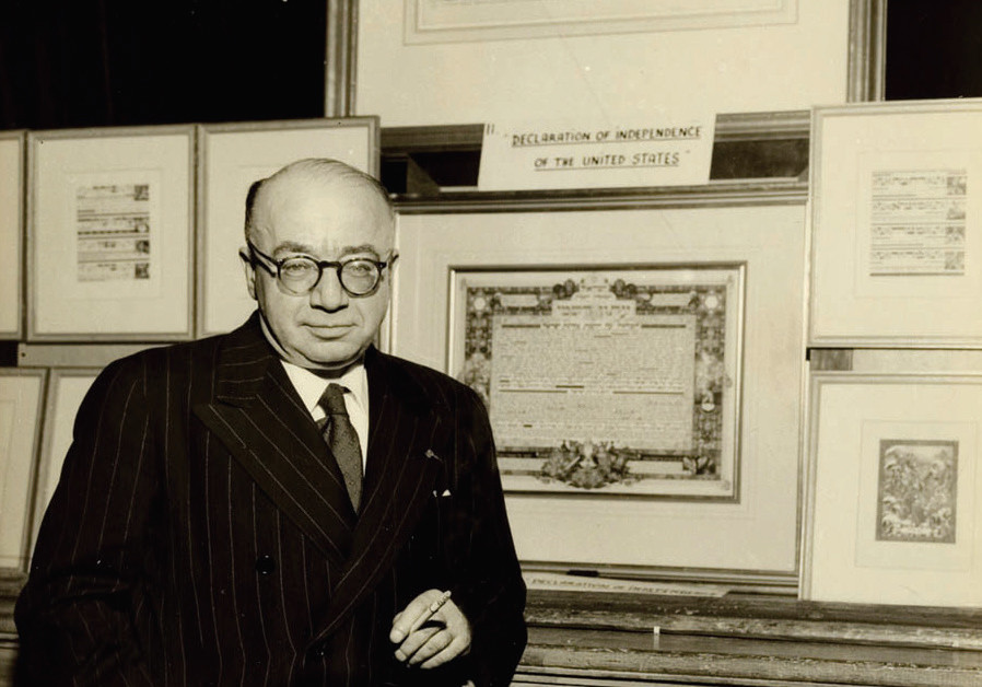 Arthur Szyk standing in front of his illuminated Declaration of Independence (top), his Proclamation of the Establishment of the State of Israel (bottom), and surrounded by Haggadah artwork; this photograph was taken on April 13, 1951 during the last exhibition in Szyk's lifetime, at Sinai Temple, Mount Vernon, New York (IRVIN UNGAR)
