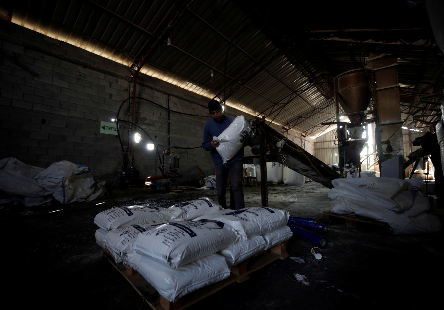 Palestinian worker carries a bag of salt at a factory near Jericho, West Bank, 2018.