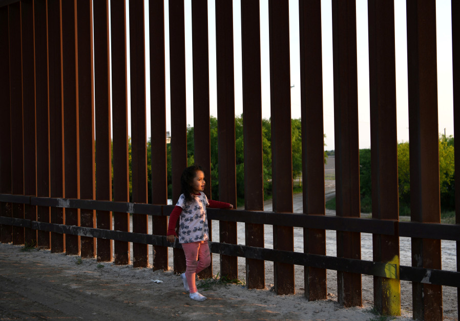 Young Central American migrant girl seeking asylum walks along border fence