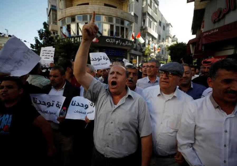 Palestinians take part in a protest calling on President Mahmoud Abbas to lift the sanctions on Gaza