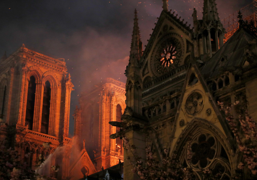 Sparks fill the air as Paris Fire brigade members spray water to extinguish flames as the Notre Dame