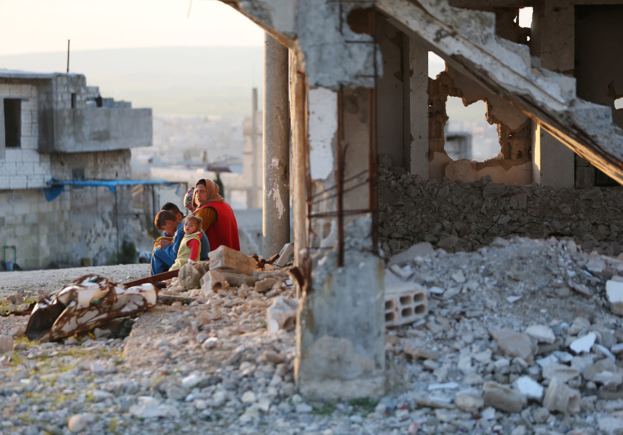 A woman sits with children on a rubble from damaged buildings in Kobani, Syria April 3, 2019