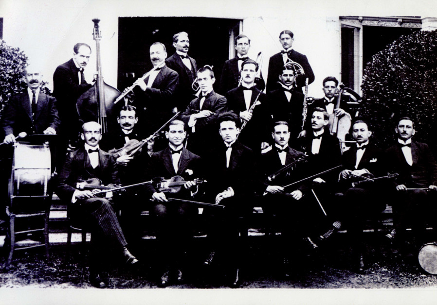 A group photograph of orchestra members with flute player Dr. Albert Menashe.
