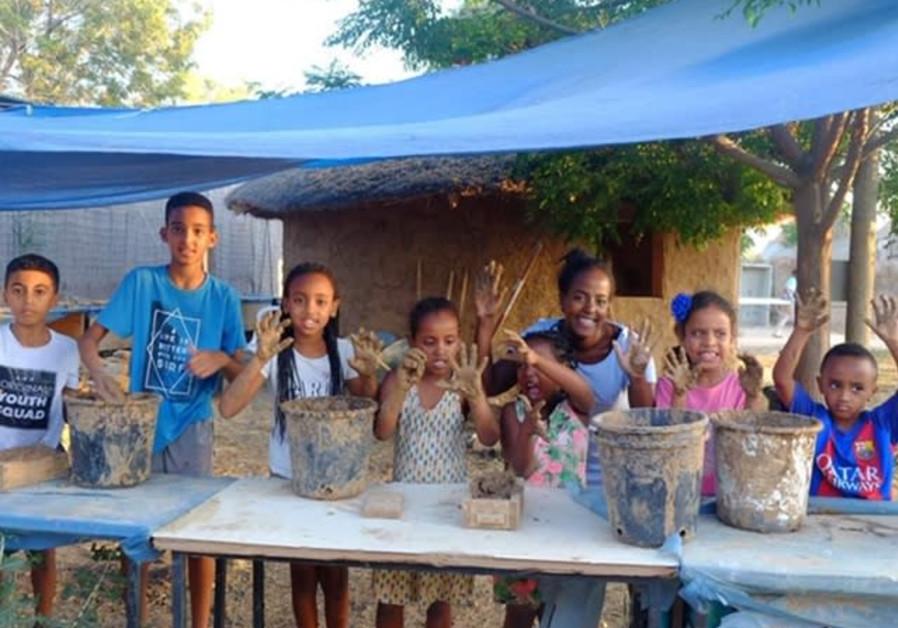 Children of the Ethiopian MAKOM community help build traditional Ethiopian mud huts at the Hineni fa