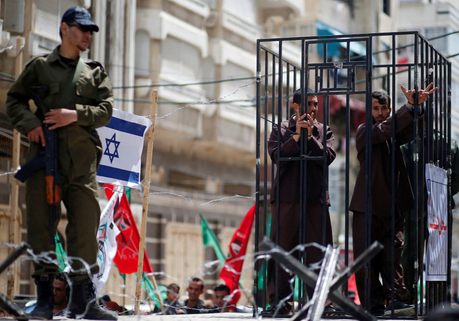 Men playing the role of prisoners during a rally marking Palestinian Prisoners' Day, in Gaza City, A