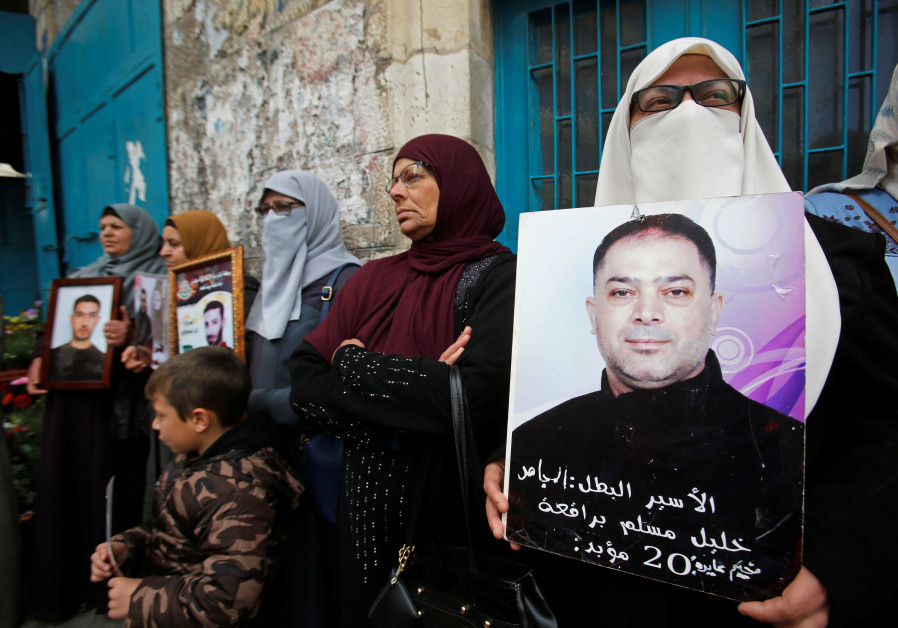 A woman holds a picture of a Palestinian prisoner held in an Israeli jail, April 19, 2019