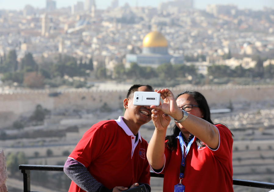 Tourists look at a mobile phone as they stand at an observation point overlooking the Dome of the Ro