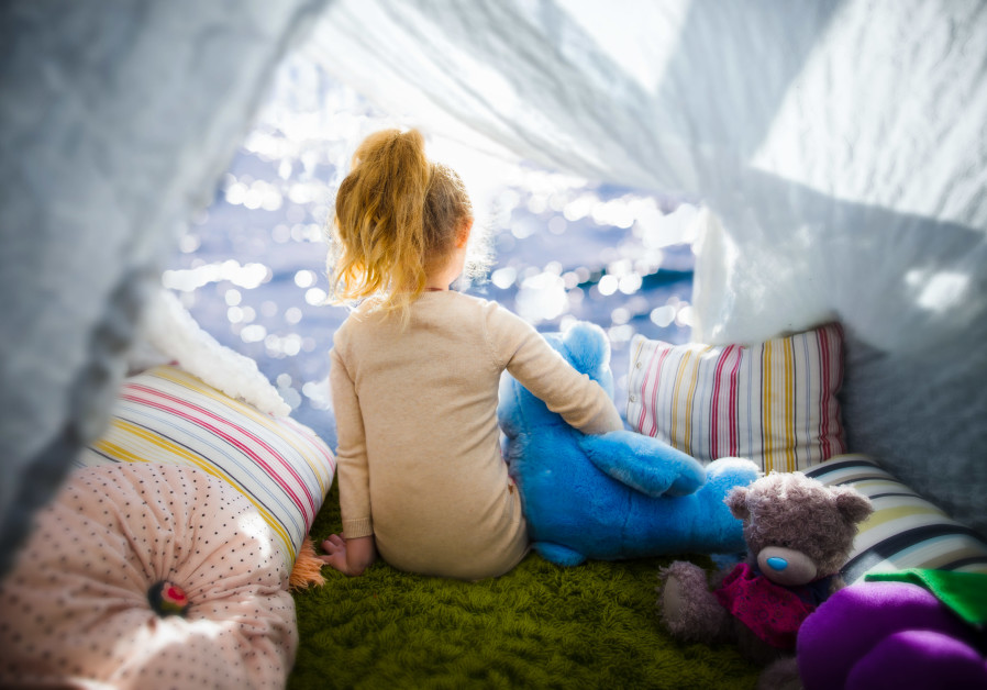Little girl with teddy bear in camp tent