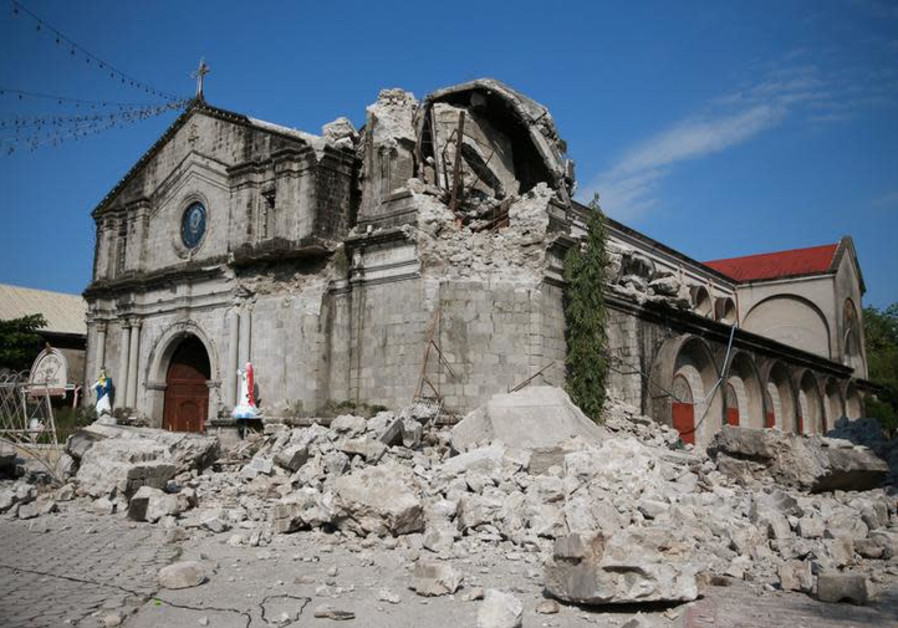 Debris and rubble surround the Santa Catalina de Alejandria Parish after an earthquake