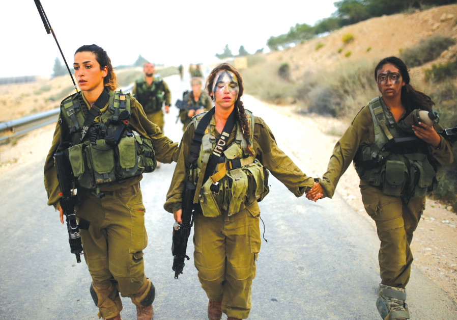 Women in an IDF combat unit help one of their fellow fighters during a training exercise