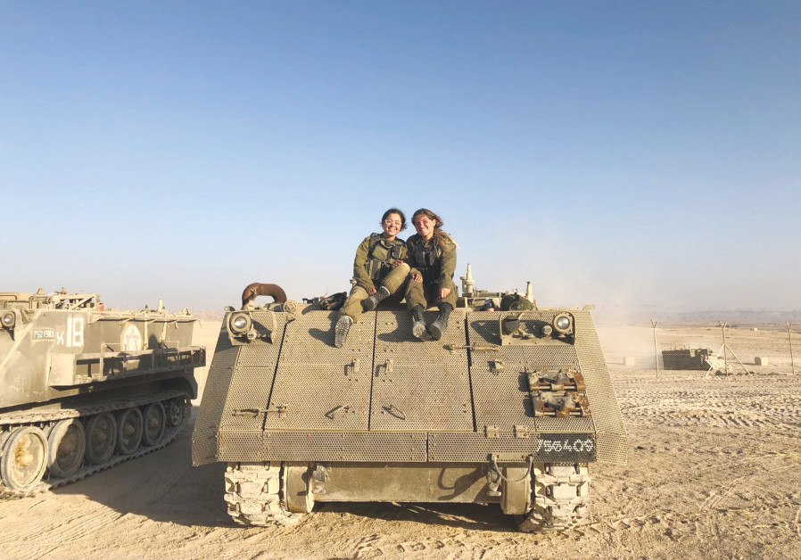 Avia (left), who is serving in the IDF's Artillery Unit, poses with a fellow artillery soldier atop a tank (Credit: IDF SPOKESMAN'S UNIT)