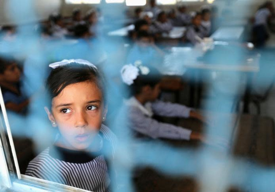 A Palestinian girl looks out of a classroom window as she attends a lesson