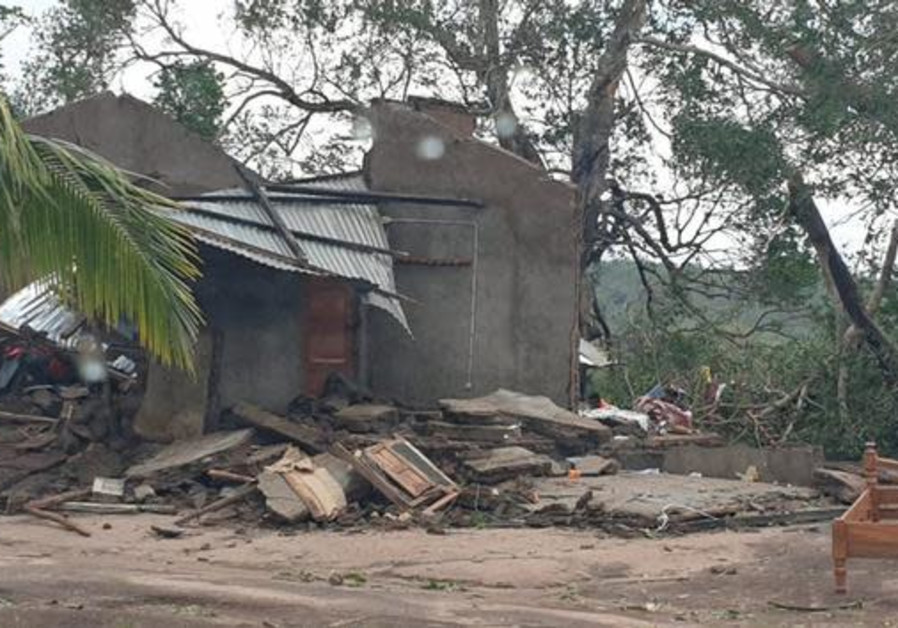 Damaged buildings are pictured from inside a vehicle after Cyclone Kenneth swept through the region