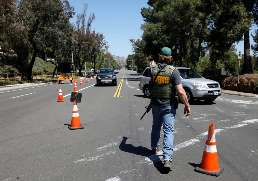 A San Diego County Sheriff's Deputy secures the scene in Poway, California