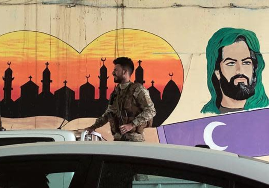 An Iraqi Popular Mobilisation Forces (PMU) member rides on the back of a pickup truck past a Shi'ite