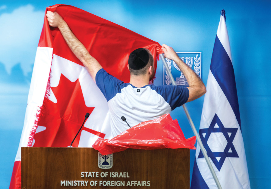 A MAN adjusts a Canadian flag next to an Israeli flag before a diplomatic meeting.