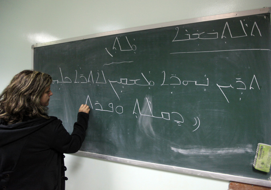 A teacher writes on the blackboard during a Syriac language class in Baghdad November 20, 2012.