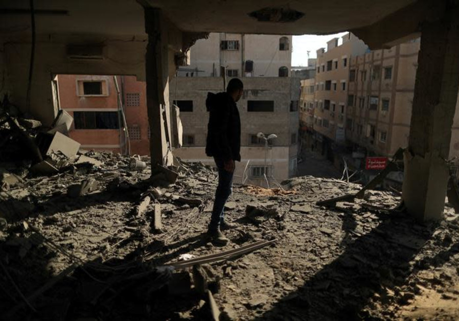 A Palestinian man inspects a building destroyed in Israeli air strikes, in Gaza City