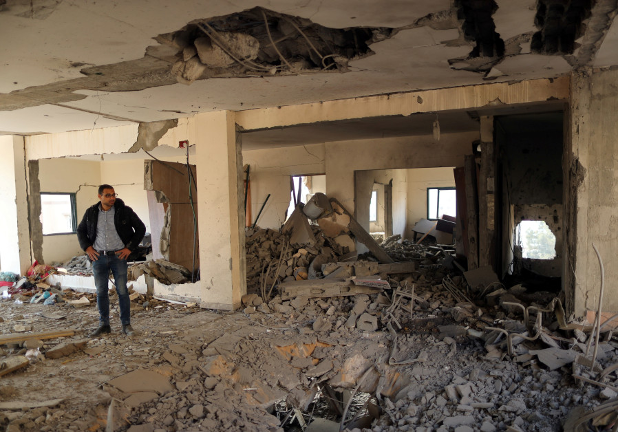 A Palestinian man looks on as he stands inside a building destroyed in Israeli air strikes, in Gaza