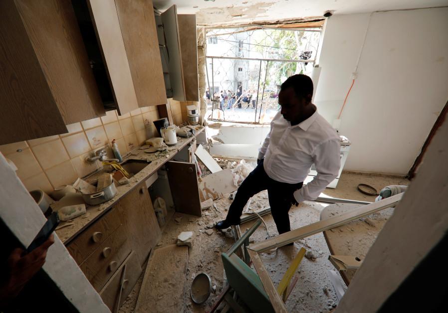 Israeli member of parliament, Gadi Yevarkan, looks at debris in a flat located in an apartment block