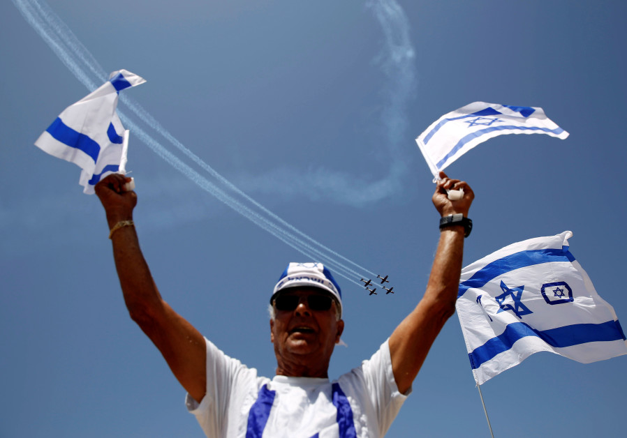 A man waves flags of Israel as Israeli Air Force planes fly in formation over the Mediterranean Sea