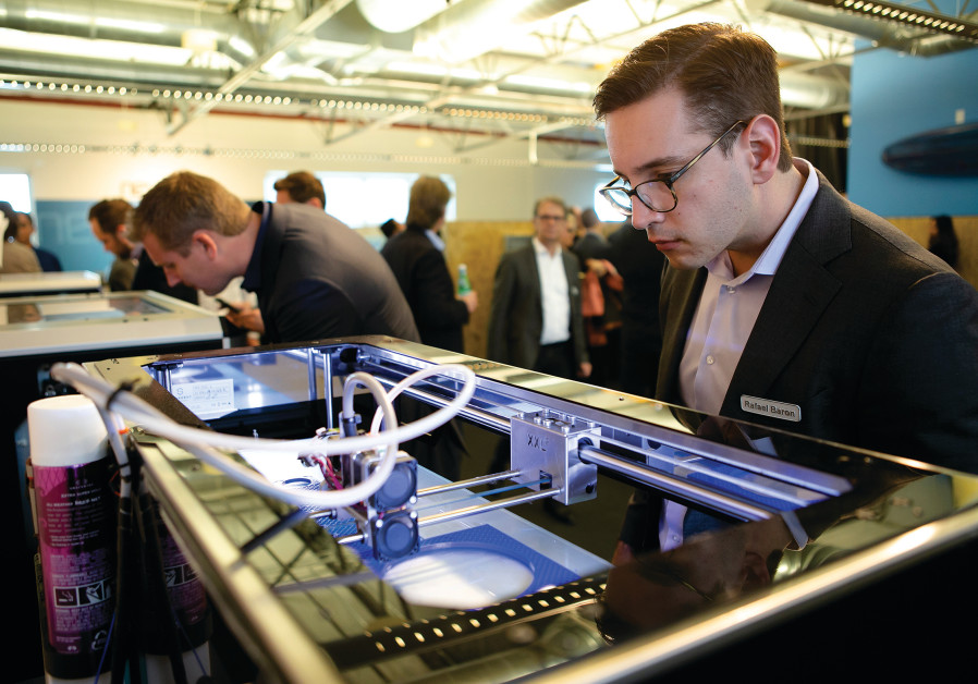 A MAN watches a 3D Printer in action while attending a conference.