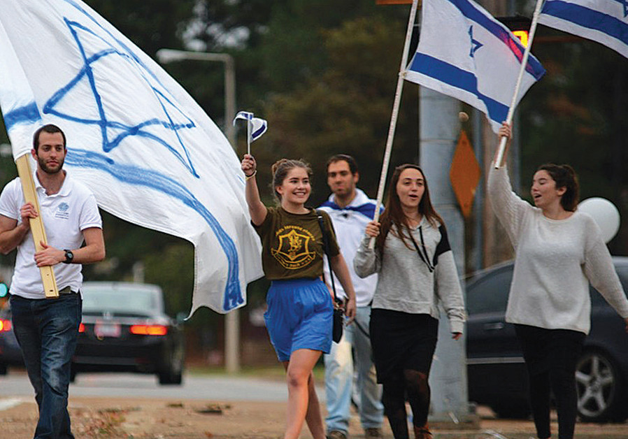 YOUTH IN Memphis wave flags and hold signs in support of Israel. (Credit: TORAH MITZION MEMPHIS)
